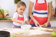 Glückliche Familie in der Küche Mutter- und Kindertochter, die Feiertagstorte oder -plätzchen für Muttertag kocht Stockbild