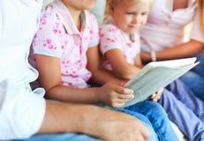 Glückliche Familie der Mutter, des Vaters und der Töchter, die einen Tablettenbaut. verwenden Stockfotos