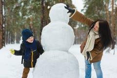 Glückliche Familie in der warmen Kleidung Lächelnde Mutter und Sohn spielen Schneebälle nahe bei einem Schneemann im Freien Das K stockbild