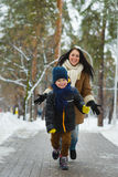 Glückliche Familie in der Winterkleidung Lächelnde Sohnläufe weg von seiner Mutter im Freien lizenzfreies stockbild