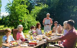 Glückliche Familie, die Abendessen oder Sommergartenfest hat stockbild