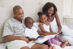Glückliche Familie, die auf Bettlesebuch liegt Stockfotos