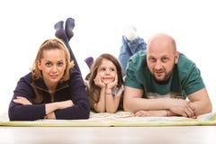 Glückliche Familie, die auf Boden legt lizenzfreies stockfoto