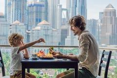 Glückliche Familie, die auf dem Balkon frühstückt Frühstückstisch mit der Kaffeefrucht und -brot croisant auf einem Balkon gegen lizenzfreies stockbild