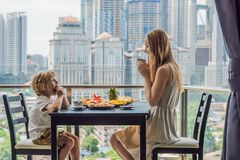 Glückliche Familie, die auf dem Balkon frühstückt Frühstückstisch mit der Kaffeefrucht und -brot croisant auf einem Balkon gegen stockfotos