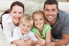 Glückliche Familie, die auf dem Fußboden liegt Stockfoto