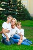 Glückliche Familie, die auf dem Gras im Sommer sitzt Stockfotos