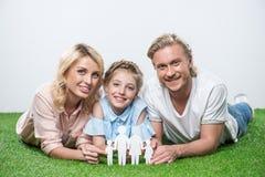 Glückliche Familie, die auf dem Gras liegt und Papierschnitt der Familie hält Stockbild