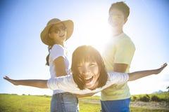 Glückliche Familie, die auf dem Gras spielt stockbild