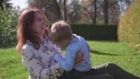 Glückliche Familie, die auf dem Rasen stillsteht Mutter mit Weichheit und Liebe spielt mit ihrem Kind, das Sohnlachen, er hat Spa stock footage