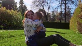 Glückliche Familie, die auf dem Rasen stillsteht Mutter mit Weichheit und Liebe umarmt ihr Kind, das Sohnlachen Glückliche Kindhe stock video footage