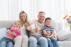 Glückliche Familie, die auf dem Sofa aufgibt Daumen sitzt lizenzfreie stockfotos