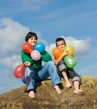 Glückliche Familie, die auf dem Stein sitzt Lizenzfreie Stockfotografie
