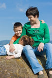 Glückliche Familie, die auf dem Stein sitzt Stockfotografie