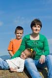 Glückliche Familie, die auf dem Stein sitzt Stockfotos
