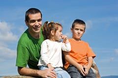 Glückliche Familie, die auf dem Stein sitzt Stockbild