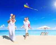 Glückliche Familie, die auf dem Strand spielt Lizenzfreie Stockfotografie