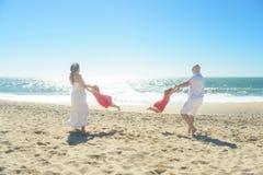 Glückliche Familie, die auf dem Strand spielt Stockfotografie