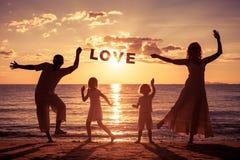 Glückliche Familie, die auf dem Strand zur Sonnenuntergangzeit steht Lizenzfreies Stockfoto