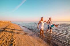 Glückliche Familie, die auf dem Ufer spielt lizenzfreies stockbild