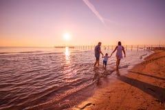 Glückliche Familie, die auf dem Ufer spielt stockfoto