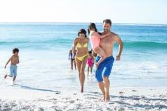 Glückliche Familie, die auf den Strand geht Lizenzfreies Stockbild