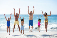 Glückliche Familie, die auf den Strand springt Stockfoto