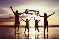 Glückliche Familie, die auf den Strand zur Sonnenuntergangzeit springt Stockfotografie