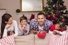 Glückliche Familie, die auf der Couch sich lehnt Stockfotos