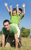 Glückliche Familie, die auf der Wiese spielt Stockbilder