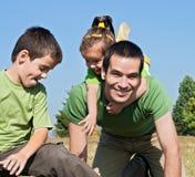 Glückliche Familie, die auf der Wiese spielt Lizenzfreie Stockfotos