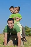 Glückliche Familie, die auf der Wiese spielt Stockbild