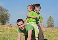 Glückliche Familie, die auf der Wiese spielt Lizenzfreie Stockbilder