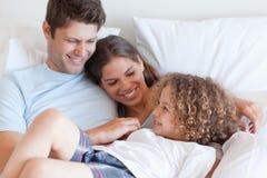 Glückliche Familie, die auf einem Bett sich entspannt Lizenzfreie Stockfotos