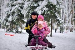 Glückliche Familie, die auf einem Schlitten im Winter sitzt stockbild
