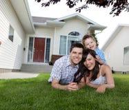 Glückliche Familie, die auf Gras liegt Stockfotos