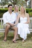 Glückliche Familie, die auf Park-Bank sitzt Stockfoto