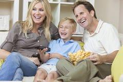 Glückliche Familie, die auf Sofa-überwachendem Fernsehen sitzt Stockfotos