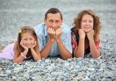 Glückliche Familie, die auf steinigem Strand, Fokus auf Vater liegt Stockfotografie