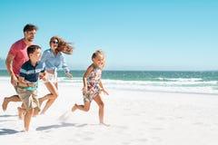 Glückliche Familie, die auf Strand läuft stockfotografie