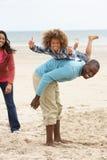Glückliche Familie, die auf Strand spielt Stockfoto