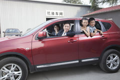 Glückliche Familie, die aus einem Auto heraus schaut stockfotografie