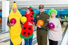 Glückliche Familie, die Bowlingkugel hält stockbild
