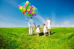 Glückliche Familie, die bunte Ballone im Freien hält. Mutter, ded und zwei Stockfotos