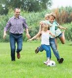 Glückliche Familie, die den Ball tritt Stockbilder