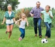 Glückliche Familie, die den Ball tritt Lizenzfreie Stockfotografie