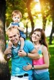 Glückliche Familie, die in den grünen Sommerpark geht Lizenzfreie Stockfotos