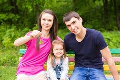 Glückliche Familie, die den Schlüssel zu ihrem neuen Haus hält stockfotografie