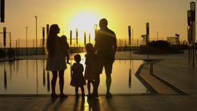 Glückliche Familie, die den Sonnenuntergang durch das Pool bewundert stockfotografie