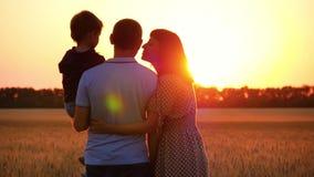 Glückliche Familie, die den Sonnenuntergang, stehend auf einem Weizenfeld aufpasst Ein Mann, der ein Kind hält Eine Frau umarmt e stock video